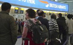 Passengers queue at a British Airways desk at Terminal 5 of Heathrow Airport in west London