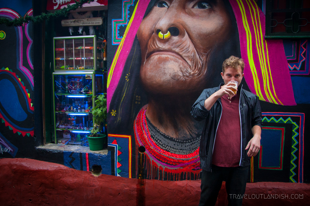 Daniel drinking chicha in front of a mural