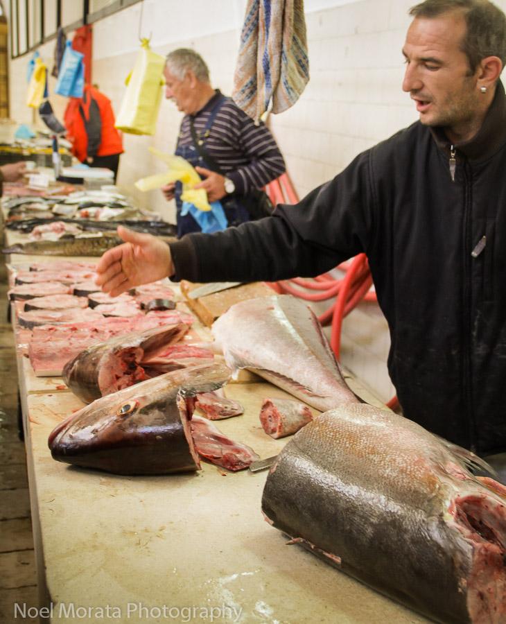 Split, Croatia fish market, a vendor is showing the different cuts