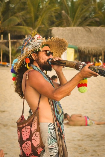 A man plays a didgeridoo on the beach.