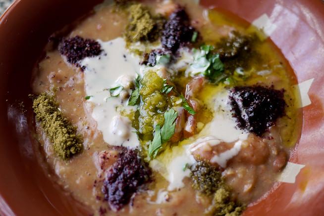 Close up of foul (ful) mudammas: the base is mashed fava beans, with cumin (yellow seasoning), sumac (purplish spice), tomatoes, and parsley.