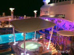 Looking down at the pool deck at night from deck 16