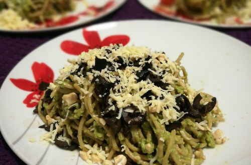 Avocado pasta on a white plate, covered with grated cheese and chopped black olives