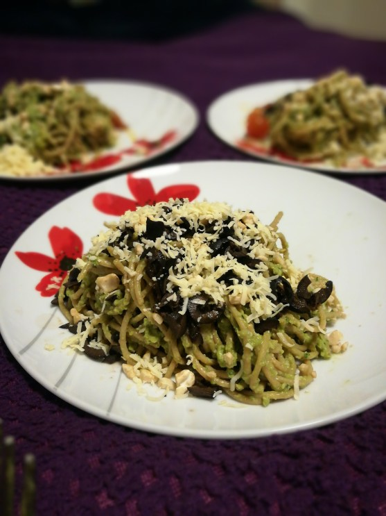A photo of spaghetti in a green avocado sauce, covered in grated cheese and chopped black olives.