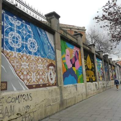 A view of a wall of graffiti in Lavapies Madrid taken from one end of the wall looking down