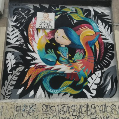 A graffiti wall in Lavapies Madrid. This image shows a girl with blue hair surrounded by colourful feather-like strokes and then black and white leaves on a black background.
