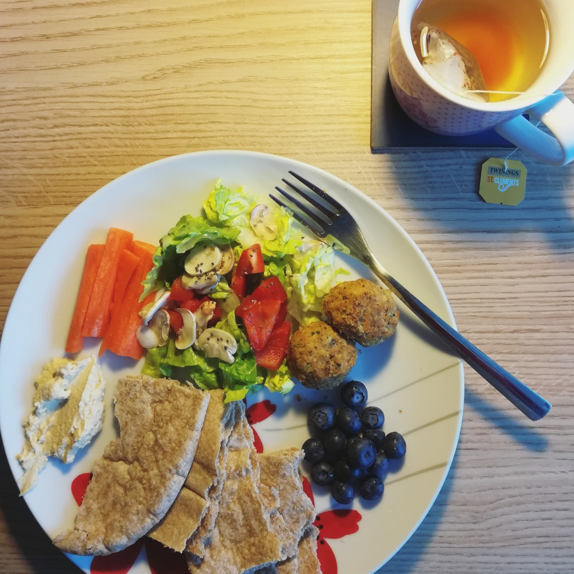 A vegan lunch made up of pitta, salad, carrot, houmous, blueberries and falafel