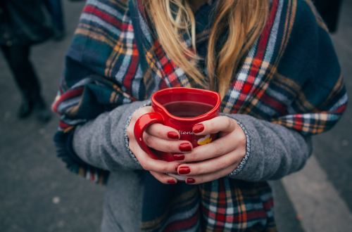 In this article about self-care, the header is a picture of a female-appearing figure, from the shoulders down, holding a red mug of tea. Photo credit to Alisa Anton