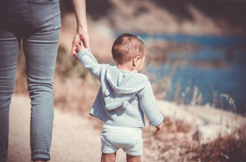 A picture of a small child holding the hand of their parent/carer or au pair, walking away from the camera