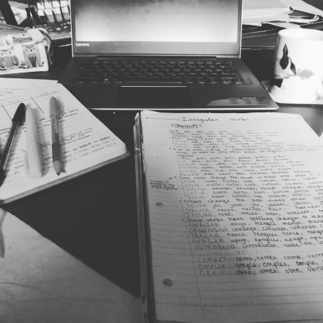 A black and white picture a laptop and notebook and pens set out on a table.