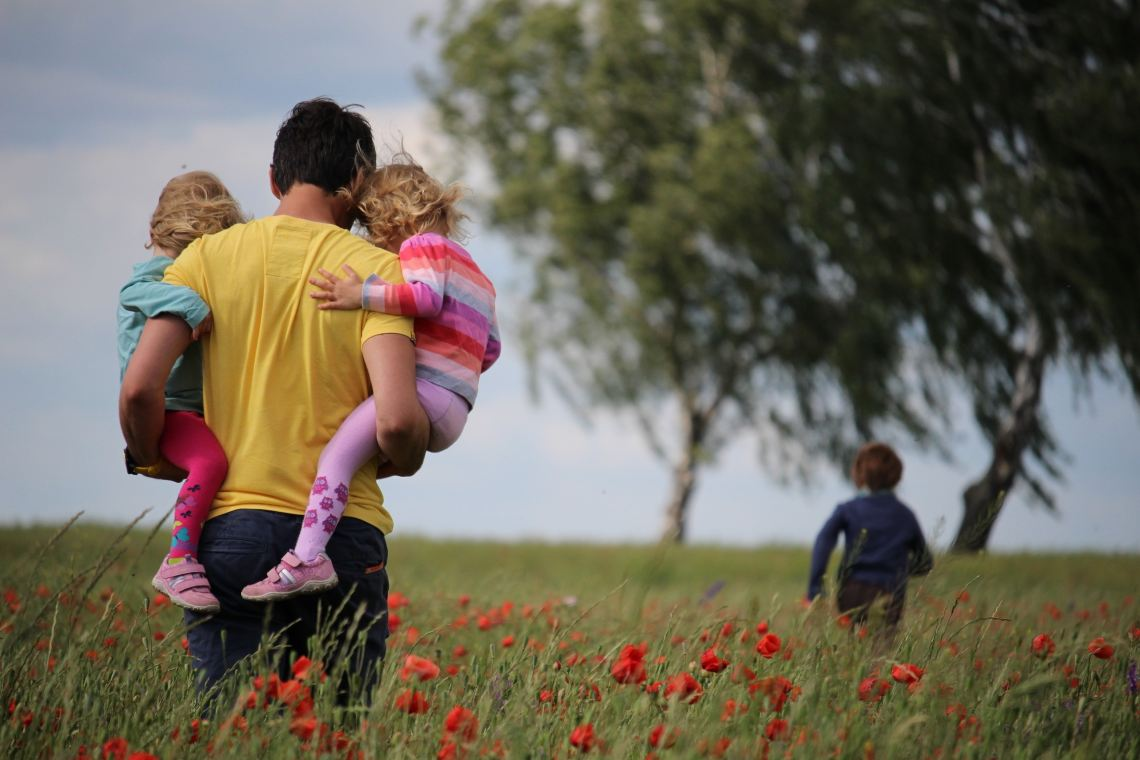 A picture of a host family walking in a field filled with red flowers.