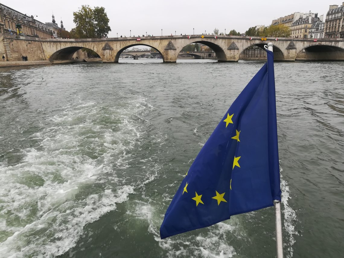 The EU flag waves in the wind at the back of a boat on the River Seine