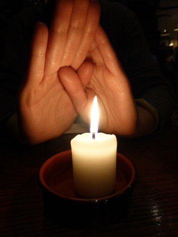 Warming hands after a chilly walk. Candle will do.