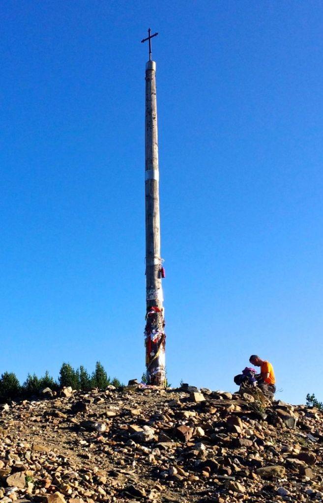 A pilgrim kneels at Cruz de Ferro. (Photo by Suzanne Ball)