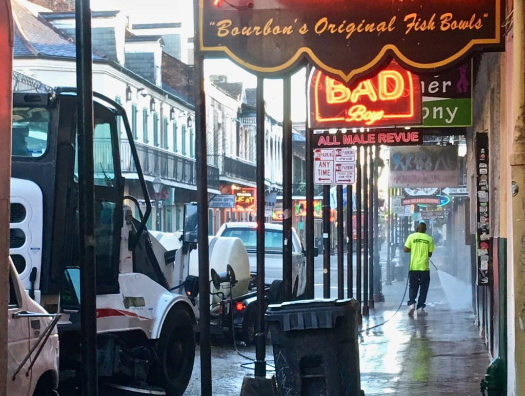 Mornings in NOLA: City workers wash down the sidewalks, while street sweepers clear out last night's beads and cups. Delivery trucks swoop in and out...they have a few hours to use the street before it comes pedestrian-only. (Photo by Suzanne Ball. All rights reserved.)