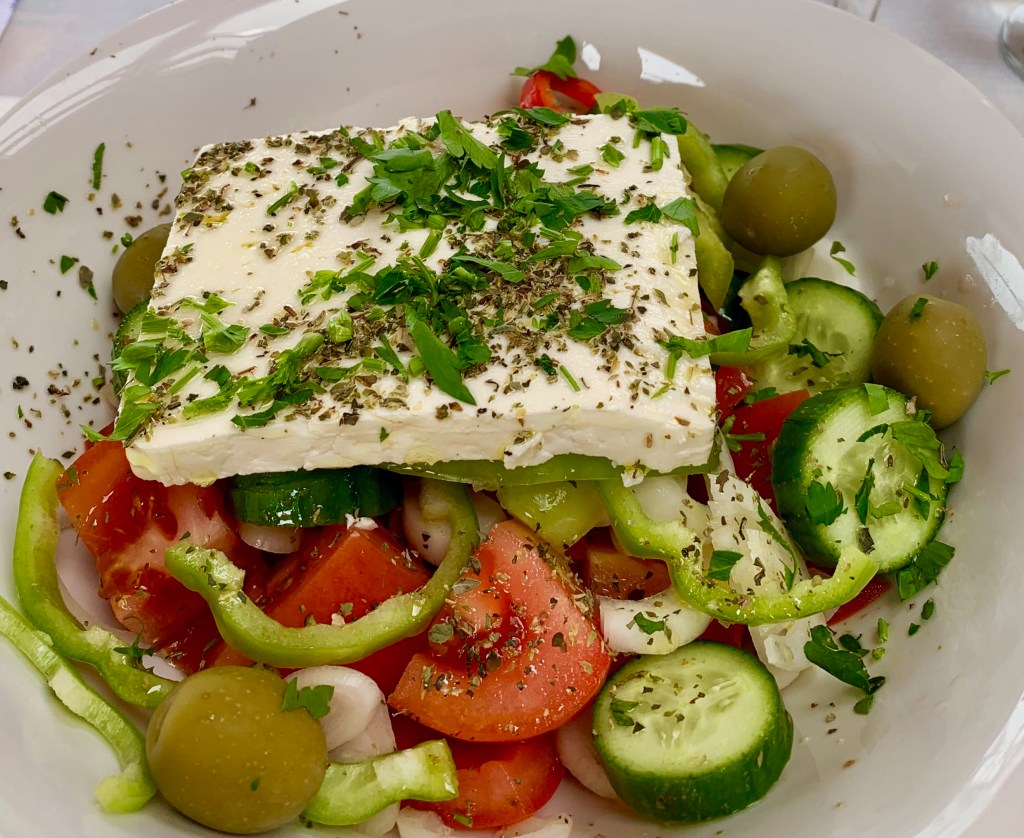 A Greek salad is topped with a slice of good feta cheese.