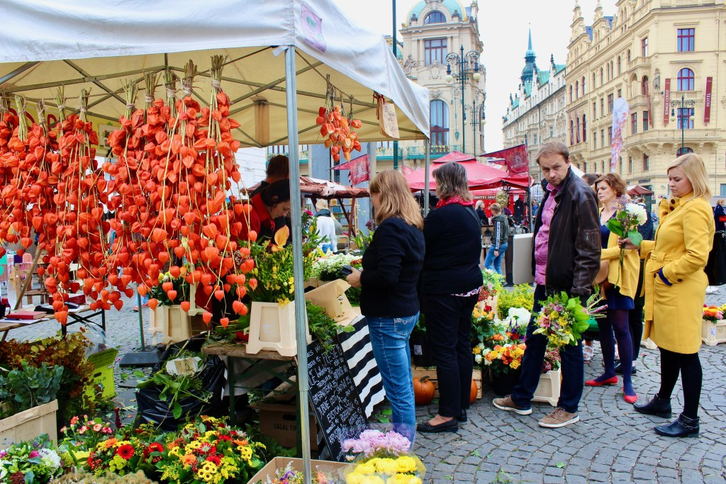 A line of people, bouquets in hand, wait at a local flower market. Aren't they one of the reasons to visit Prague in the autumn??