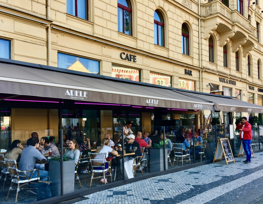 Locals relax at a Prague cafe, without long tourist lines.