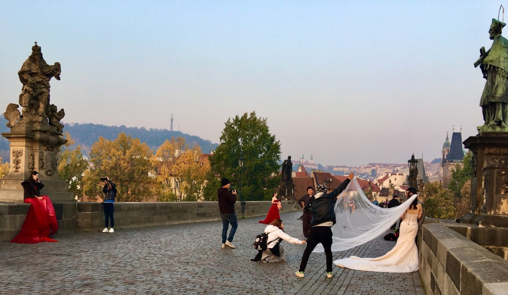 Brides pose on Charles Bridge in the chilly morning air.