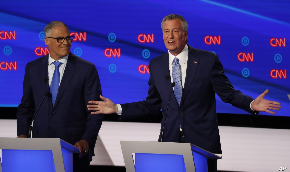 Washington Gov. Jay Inslee listens as New York City Mayor Bill de Blasio speaks during the second of two Democratic presidential primary debates hosted by CNN, July 31, 2019, in the Fox Theatre in Detroit.