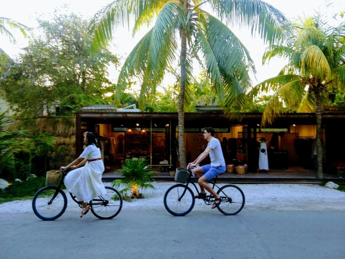Bike riders in Tulum on Tulum Beach Road in front of a boutique