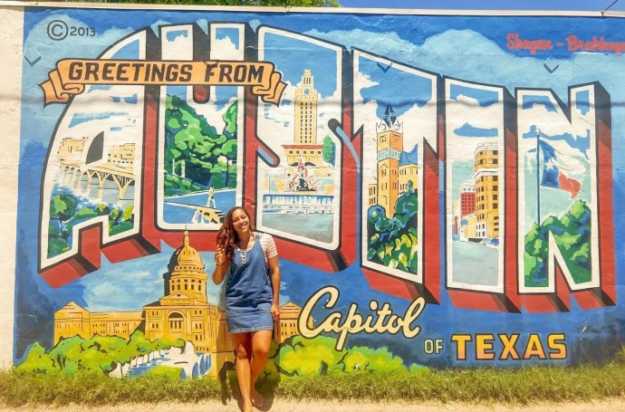 Sarah Fay in Austin Texas in front of mural of a Postcard from Austin Texas.