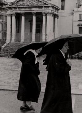 Nuns in the rain walking along the Grand Canal in Venice, Italy.