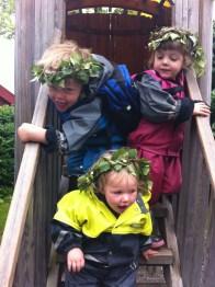 Leon, Frida and Lottie wearing their midsummer laurel crowns at Skansen in Stockholm.