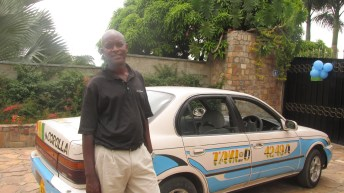 Photo of Taxi driver Dominick standing by his taxi.