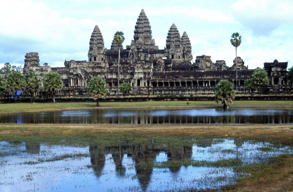 Image of Angkor Wat temple reflected on the water before it.