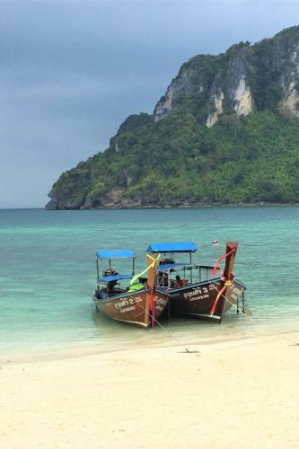 The iconic Thailand long boats have provided transportation for centuries. The boats of Thailand with long tail motor are beautiful to see. Click to learn what riding in a longboat is truly like. #Thailand #SoutheastAsia #Thailandbeaches #beach #longboats #travel #Thaiboat