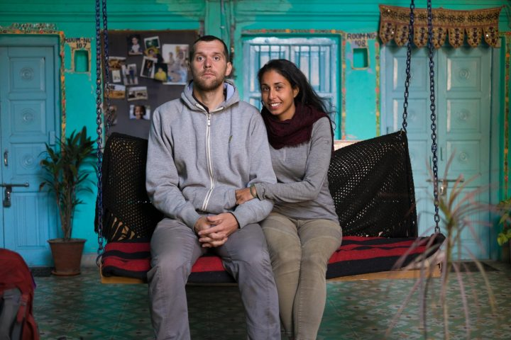 A couple sits on a seat in a blue room