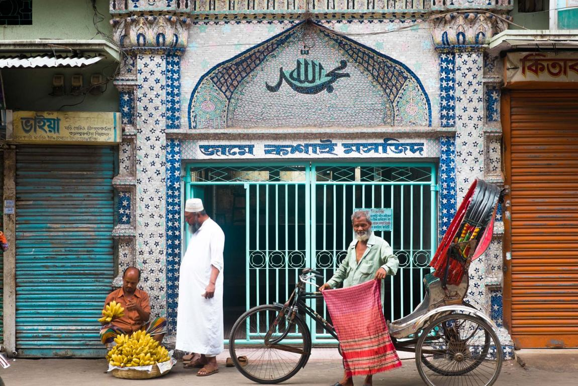 Three men standing outside a mosque entrance in Bangladesh