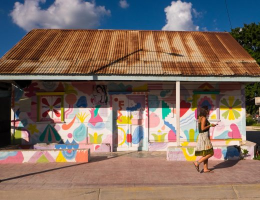 Woman walks past bright coloured building in Bacalar Mexico