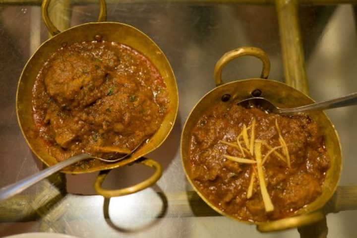 Two dishes of Shaktora Gosht curry on a glass table