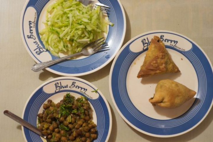 Plates of samosas, shredded cucumber and chickpeas in Bangladesh