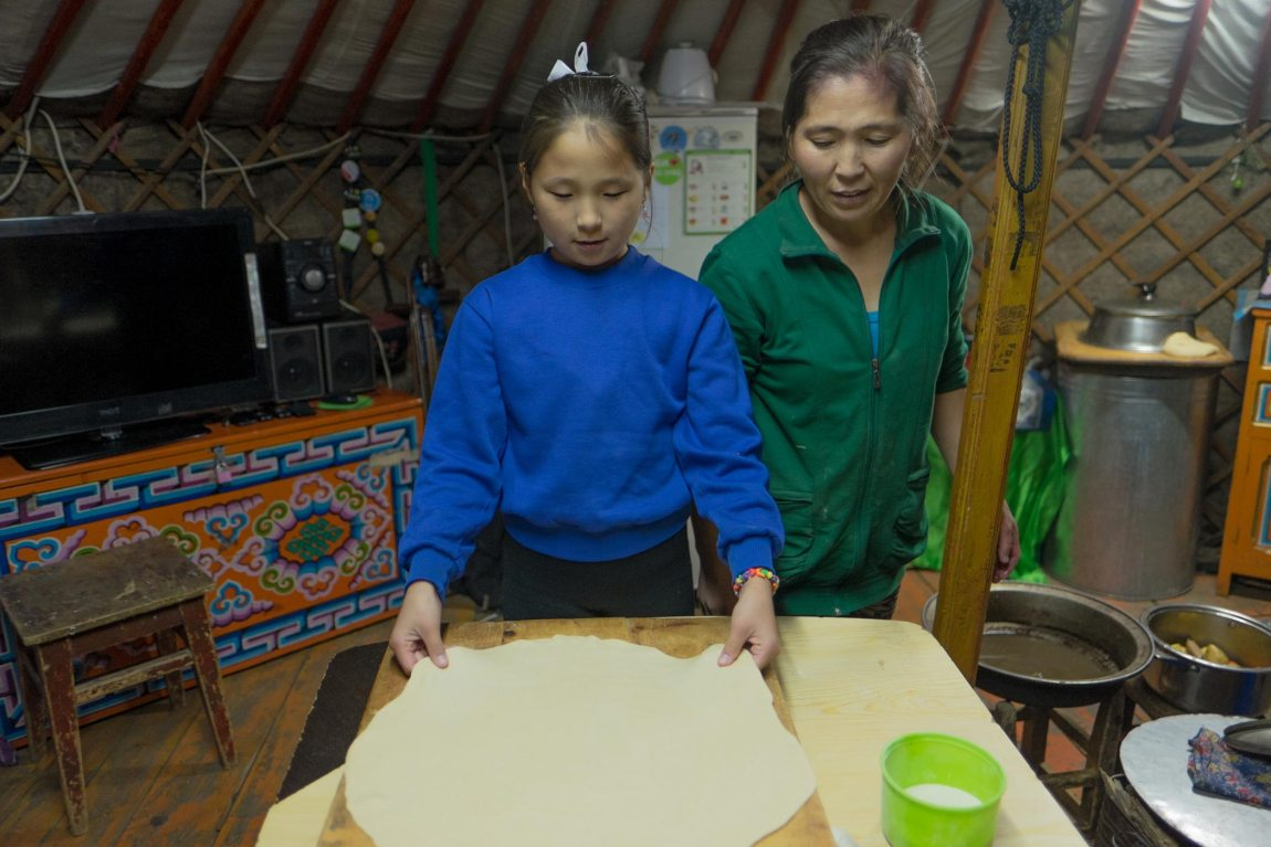 A girl and her mother make the dough for Tsuivan in Mongolia.