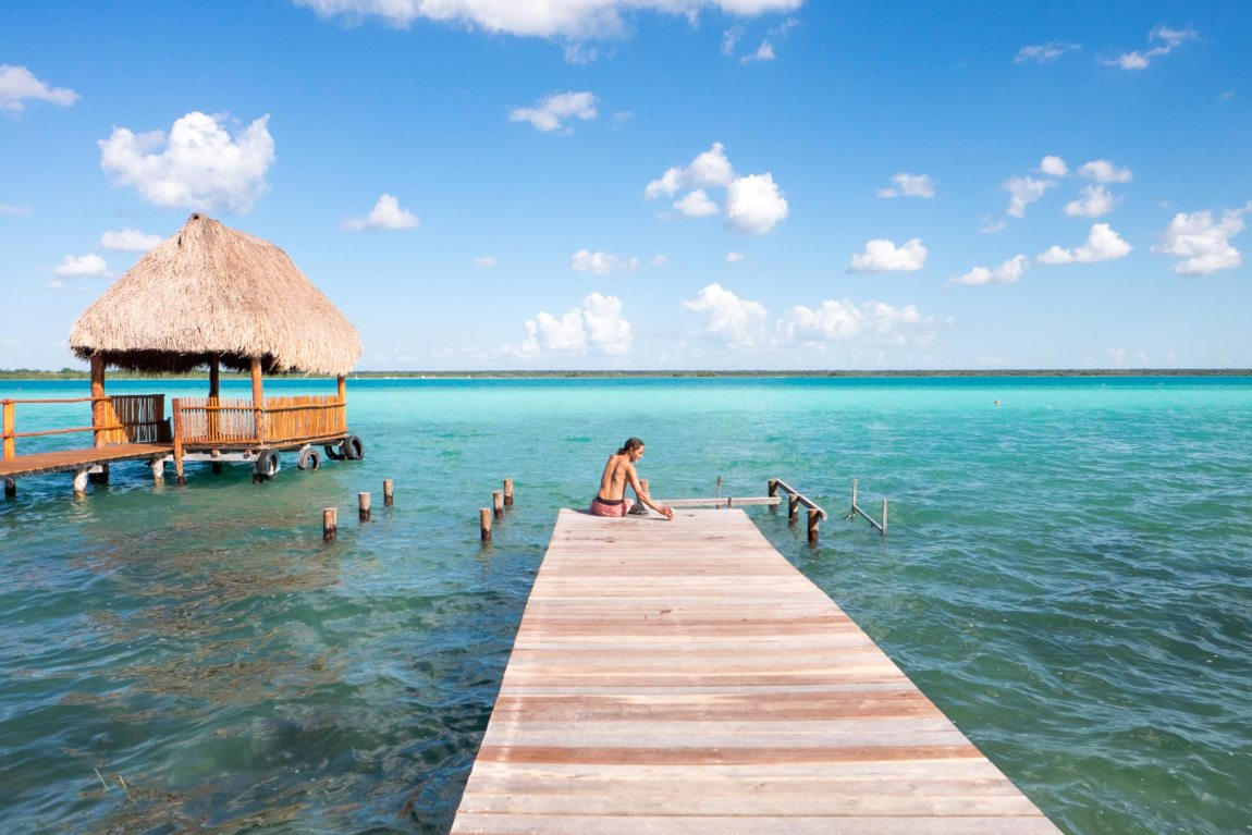 A man sits at the end of a dock at Lake Bacalar in Mexico