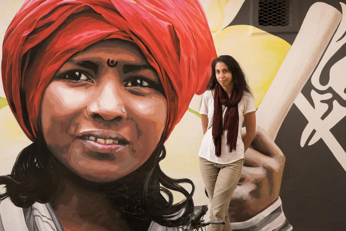 A woman stands in front of a street mural in Varanasi