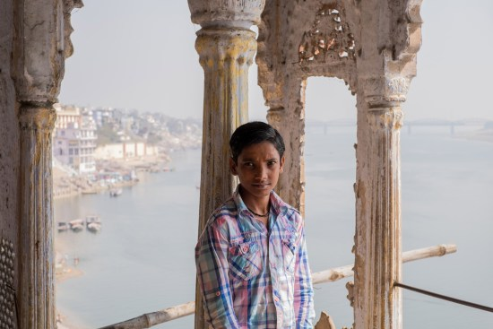 A boy stands on a balcony in Varanasi