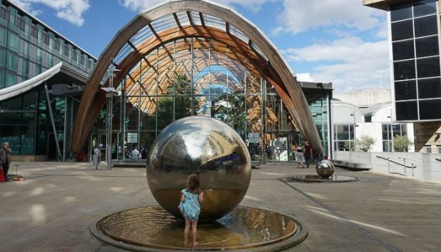 child playing in the water surrounding the steel balls in the Sheffield Peace Gardens