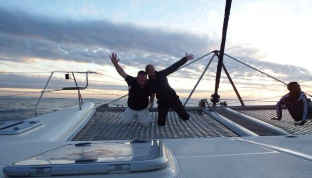 People on a catamaran at sunset