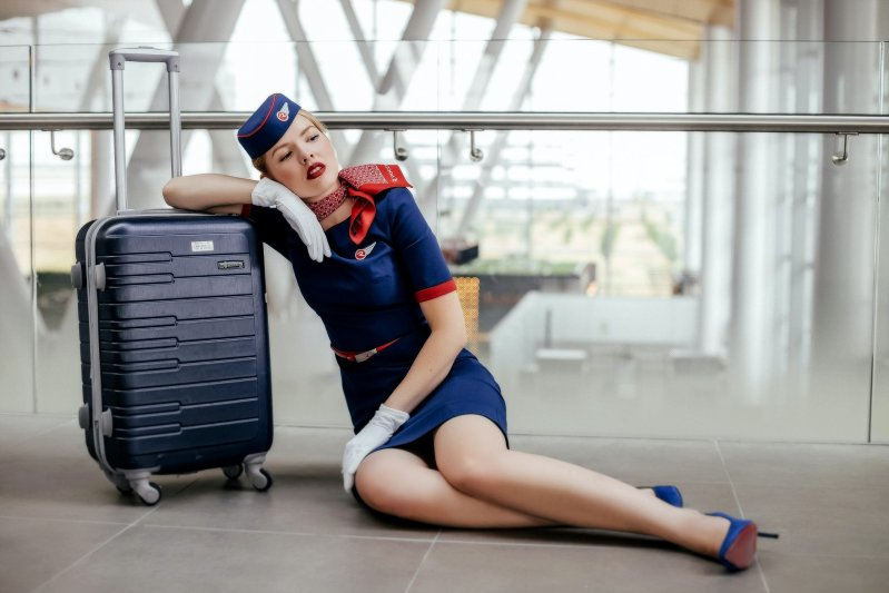 hostess seduta in aeroporto con valigia