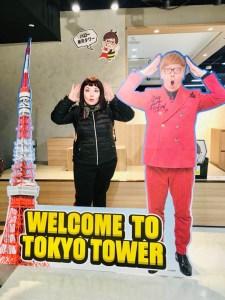 Cineturismo a tema otaku a Tokyo marzia all'interno della Tokyo Tower di Tokyo in posa davanti alla sagoma della torre bianca e rossa