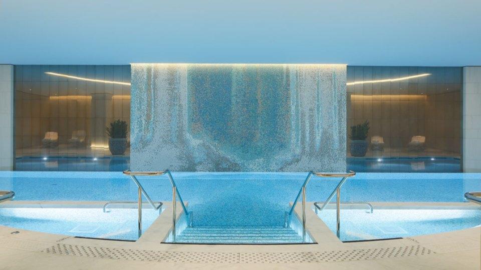 Pool facilities with a huge waterfall (Image Source: The Peninusla Paris / paris.peninsula.com)