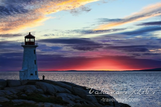 The famous Peggy's Cove lighthouse in the fire red light of the sunset. It was taken right before the sun was completely gone