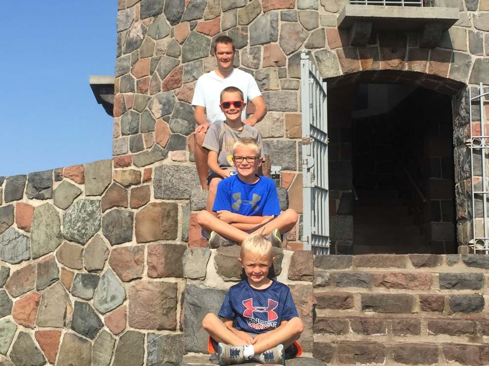 The Best Things to Do in Duluth MN with your Family featured by top US family travel blog, Travel with a Plan: image of a Family sitting on the steps at the base of Enger Tower