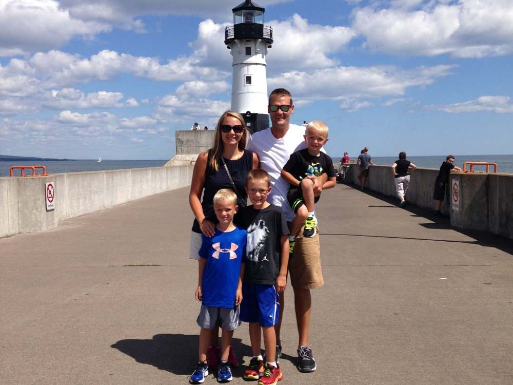 The Best Things to Do in Duluth MN with your Family featured by top US family travel blog, Travel with a Plan: image of a Family at Canal Park lighthouse