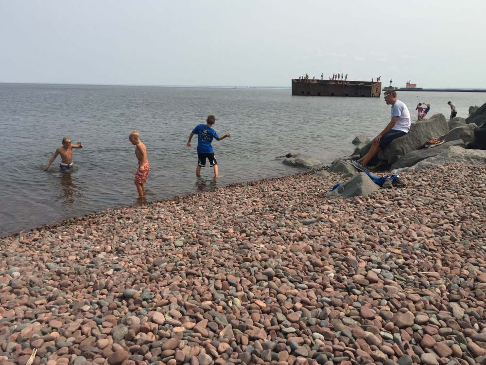 The Best Things to Do in Duluth MN with your Family featured by top US family travel blog, Travel with a Plan: image of Boys skipping rocks along the Lakewalk