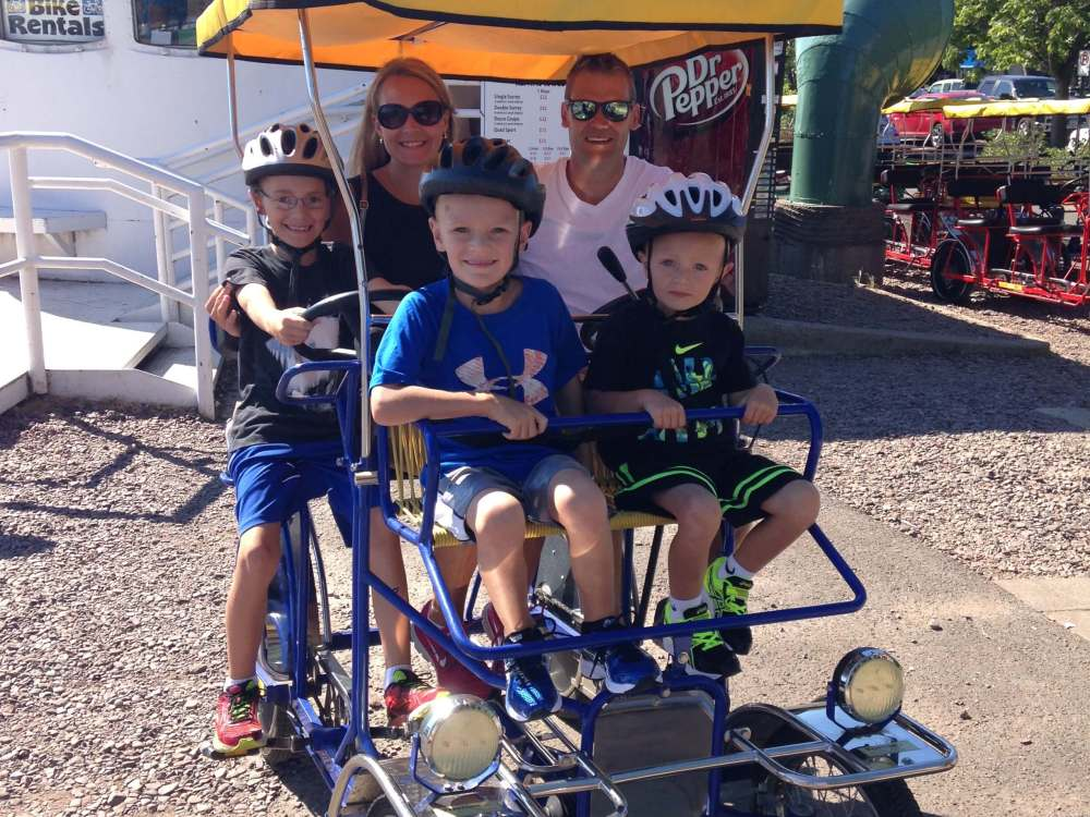 The Best Things to Do in Duluth MN with your Family featured by top US family travel blog, Travel with a Plan: image of a Family on a Wheel Fun surrey rental